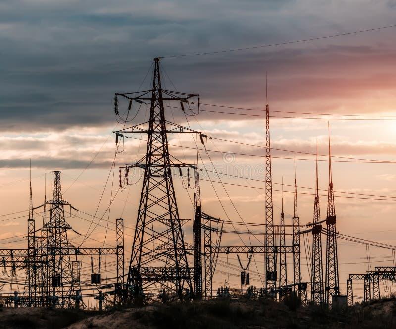 Elektrische Nebenstelle der Verteilung mit Stromleitungen und Transformatoren, bei Sonnenuntergang lizenzfreies stockbild