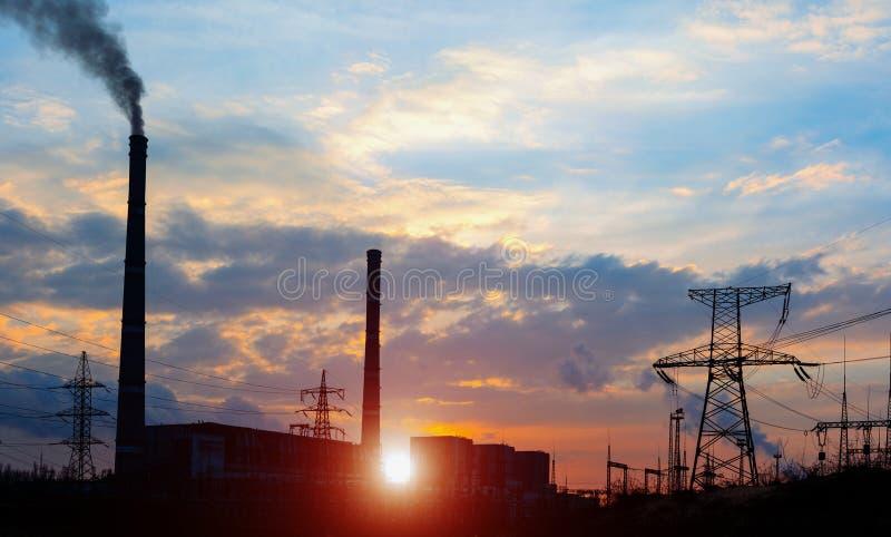 Elektrische Nebenstelle der Verteilung mit Stromleitungen und Transformatoren, bei Sonnenuntergang stockbild