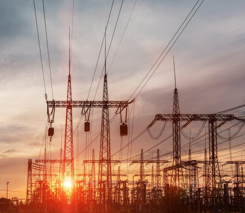 Elektrische Nebenstelle der Verteilung mit Stromleitungen und Transformatoren, bei Sonnenuntergang stockfotografie