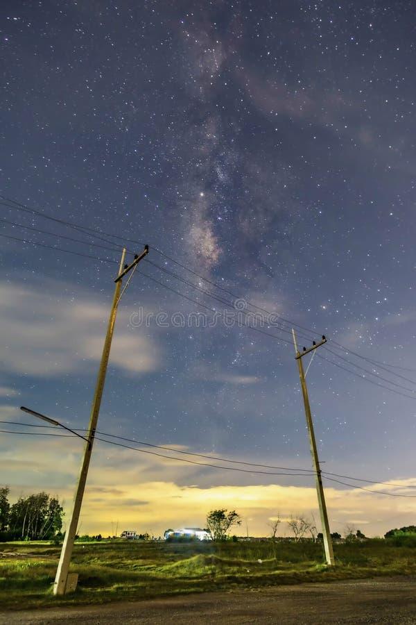 Elektrische Pfosten in der Nachtzeitlandschaft, im Himmel mit Sternen und in den schönen Wasserbrotwurzelszenen, Wolken unterhalb stockbild