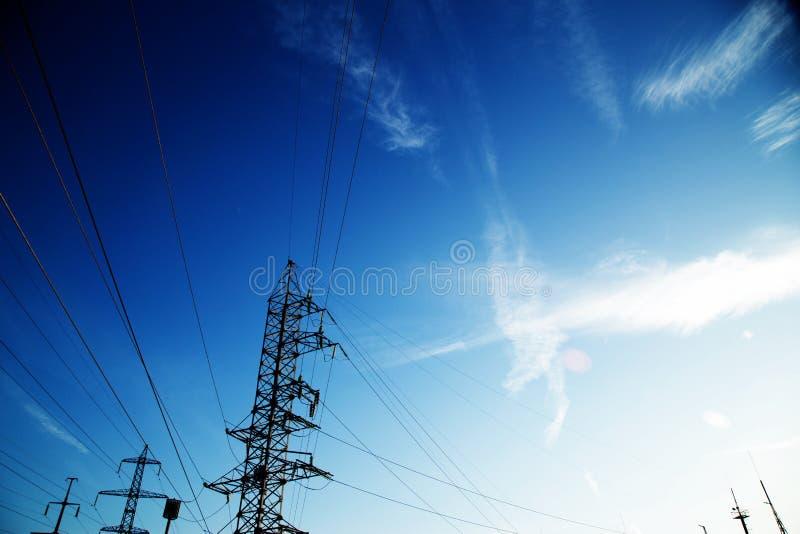Elektrische polen en draden tegen een achtergrond van blauwe hemelwolken royalty-vrije stock foto's