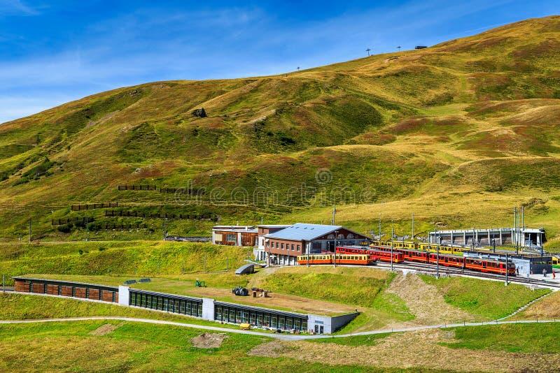 Elektrische rode toeristentreinen in de post, Bernese Oberland, Zwitserland royalty-vrije stock foto