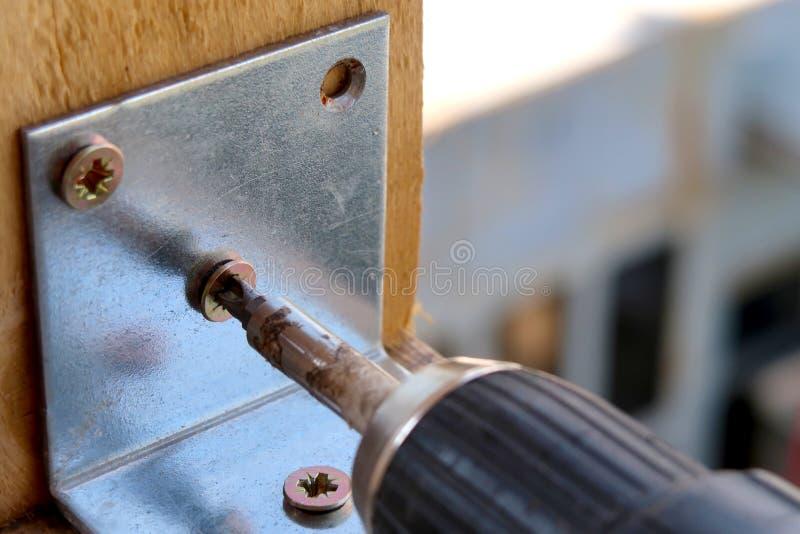 Elektrische schroevedraaier die op een metaal schroeven die fixeerstof in het nauw drijven royalty-vrije stock afbeeldingen