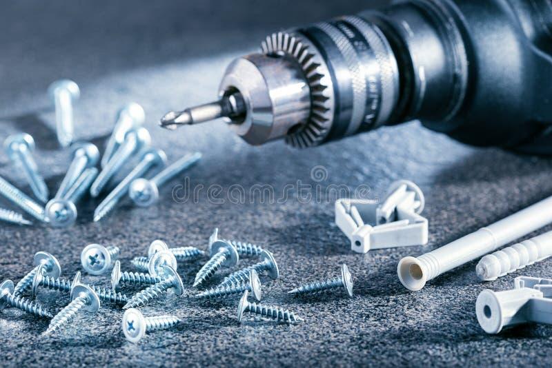 Elektrische schroevedraaier en diverse schroeven op grijze oppervlakte stock afbeelding