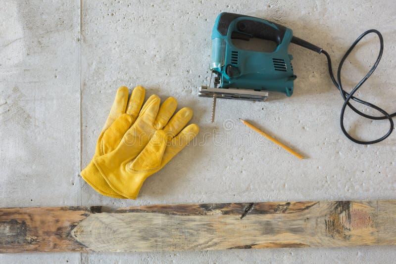 Elektrische Spannvorrichtungssäge und gelbe Handschuhe stockfotografie