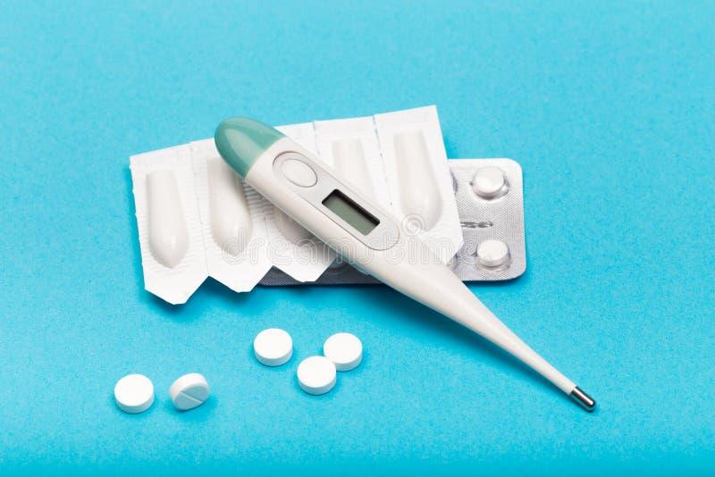 Elektrische thermometer, plastic pakken zetpillen en tabletten op blauwe achtergrond stock afbeeldingen