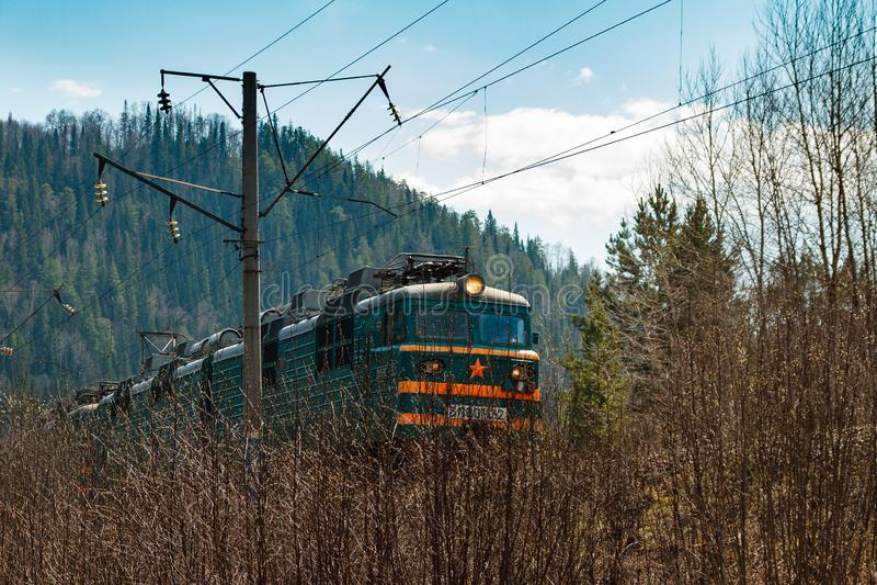 Elektrische trein RZHD op berg bosachtergrond in de lente royalty-vrije stock afbeelding