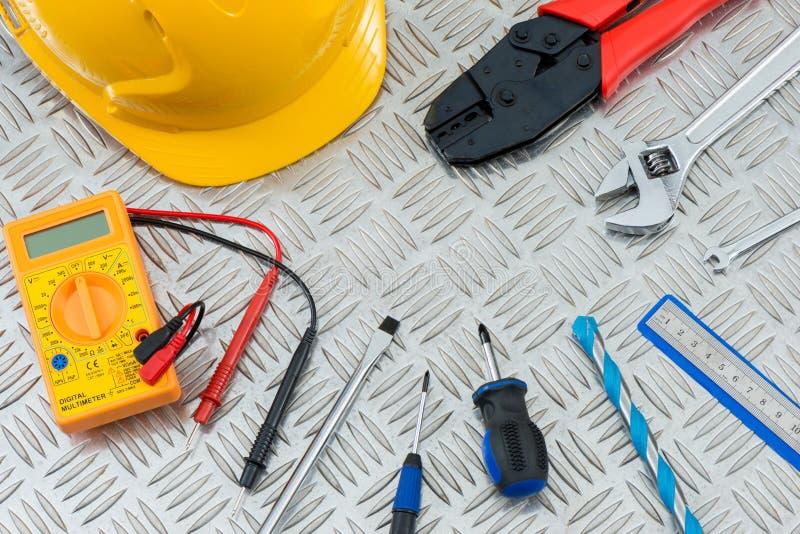 Elektrische und Zimmerei-Werkzeuge auf Metallwarzenblech lizenzfreies stockfoto