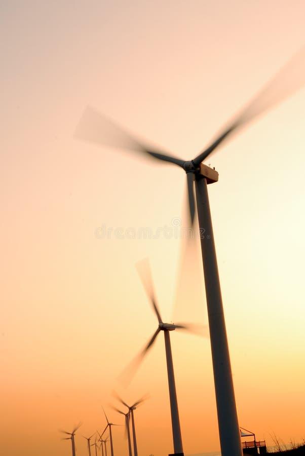 Elektrische windmolen bij zonsondergang stock foto's