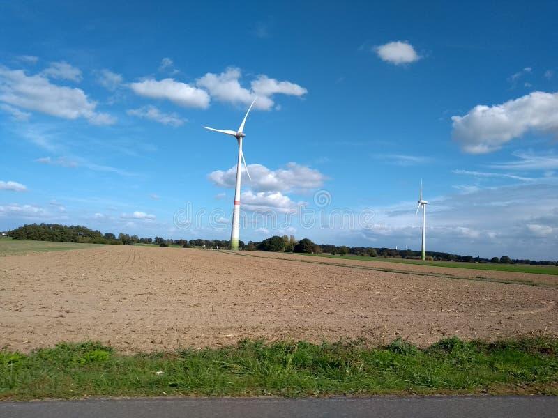 Elektrische windmolenturbine over Duitse landbouwgebieden stock afbeeldingen
