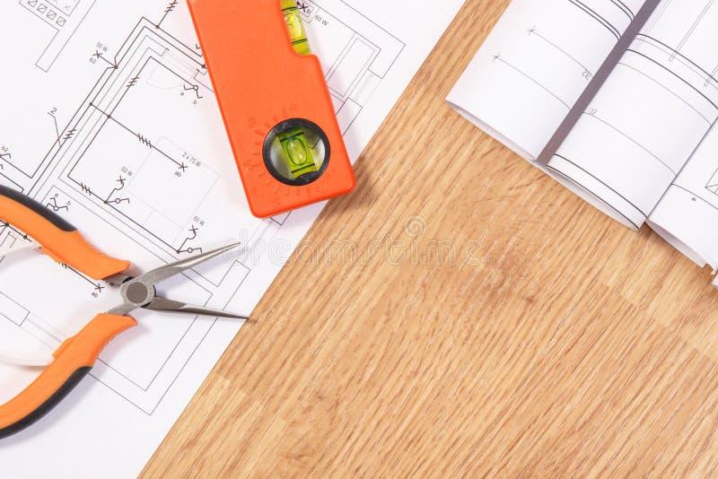 Elektrische Zeichnungen oder Diagramme, orange Arbeitswerkzeuge für Gebrauch in den Ingenieurjobs, Kopienraum für Text an Bord lizenzfreie stockfotografie