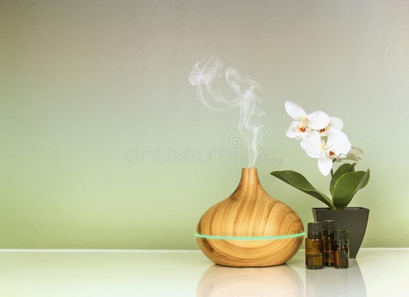 Elektrischer Aromadiffusor der ätherischen Öle, Ölflaschen und Blumen auf grüner Steigungsoberfläche mit Reflexion lizenzfreies stockfoto
