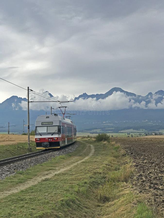 Elektrischer Bahnzug Tatra mit hohem Tatras im backround, Slowakei lizenzfreies stockfoto