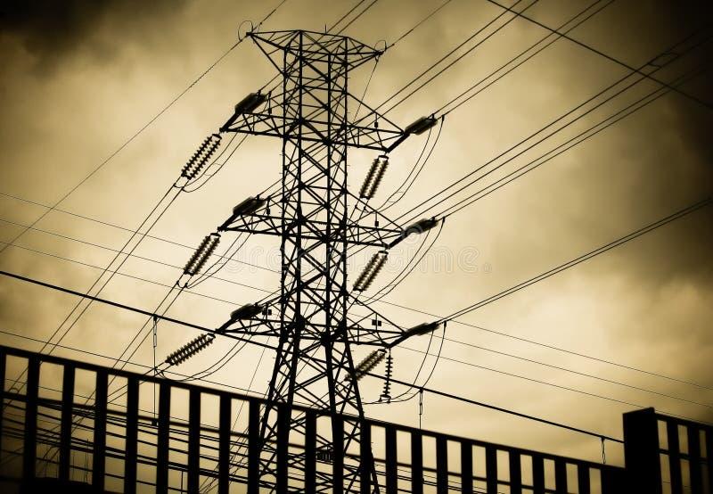 Elektrischer Hochspannungsturm oder Mast und Stromleitungen Schattenbild gegen dunklen bewölkten Himmel lizenzfreies stockfoto