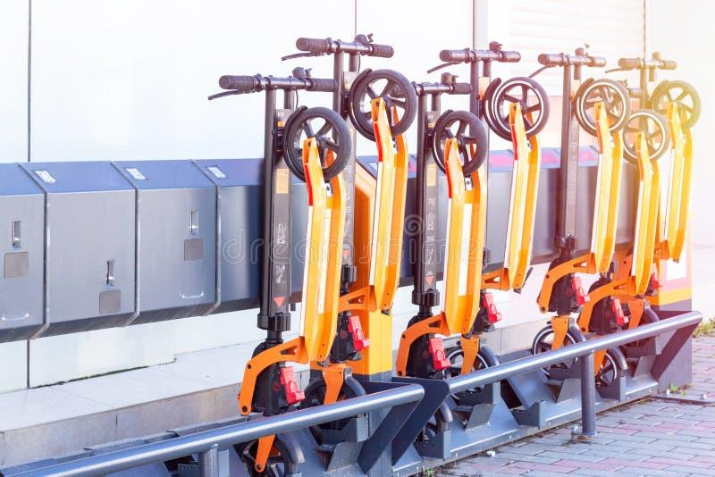 Elektrischer Kick-Roller im gemeinsamen Parkplatz Scooter-Verleihstation Neues Geschäftsvorhaben Leute Hände mit Smartphone lizenzfreie stockfotografie