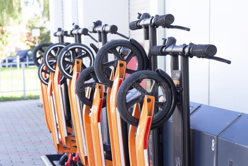 Elektrischer Kick-Roller im gemeinsamen Parkplatz Scooter-Verleihstation Neues Geschäftsvorhaben Leute Hände mit Smartphone stockfotografie