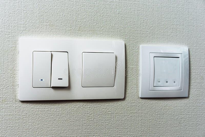 Elektrischer Lichtschalter und Sockel auf der leeren Wand, Sockel der elektrischen Leistung und Stecker geschaltet Komforthaus We lizenzfreies stockfoto
