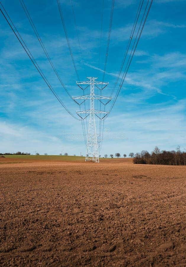 Elektrischer Nebenstellenstrommast, Zustand und Hochspannungsleitungsschattenbild mit blauem bew?lktem Himmel bei Sonnenuntergang lizenzfreie stockfotos
