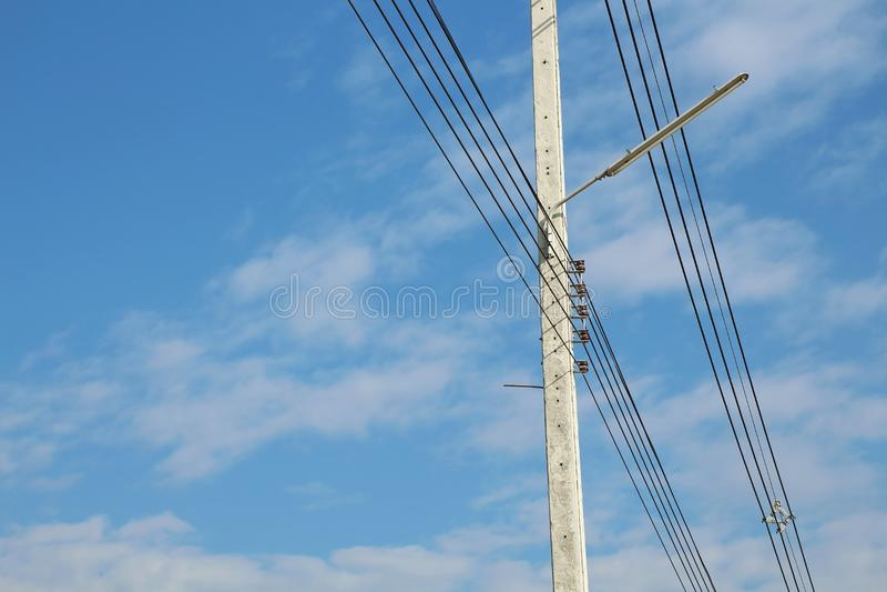 Elektrischer Pfosten und Stromleitungen mit schönem blauem Himmel stockbild
