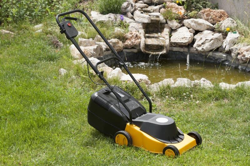 Elektrischer Rasenmäher im schönen Garten lizenzfreie stockfotos