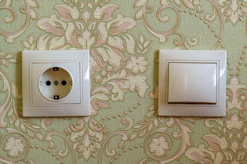 Elektrischer Schalter und Stecker auf Wand stockbilder