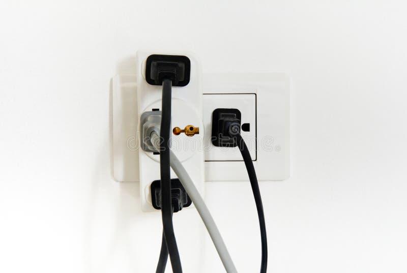 Elektrischer Stecker und Sockel überbelastet auf weißem Hintergrund lizenzfreies stockbild