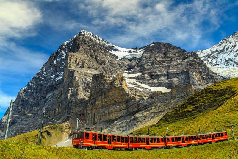 Elektrischer touristischer Zug und Nordgesicht Eiger, Bernese Oberland, die Schweiz stockbild