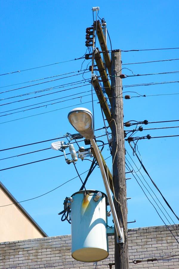 Elektrischer Transformator befestigt zum elektrischen Beitrag mit elektrischen Leitungen lizenzfreie stockfotografie