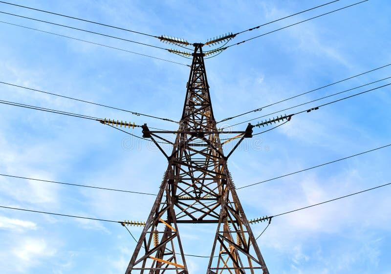 Elektrischer Turm auf dem blauen Hintergrund des bewölkten Himmels, symmetrischer Hintergrund lizenzfreie stockfotos