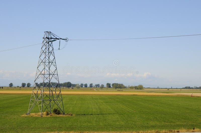 Elektrischer Turm unter Bauernhoffeldern stockfoto
