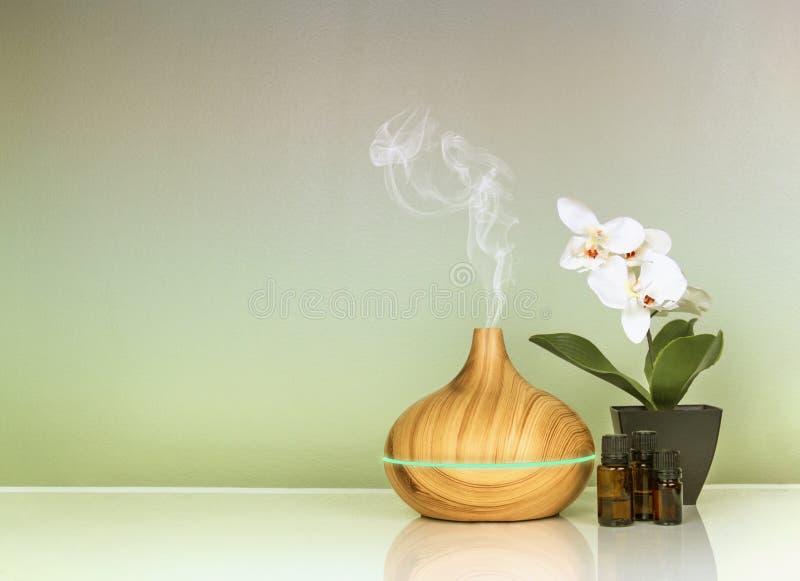 Elektrisk aromdiffusor för nödvändiga oljor, oljaflaskor och blommor på grön lutningyttersida med reflexion royaltyfri foto