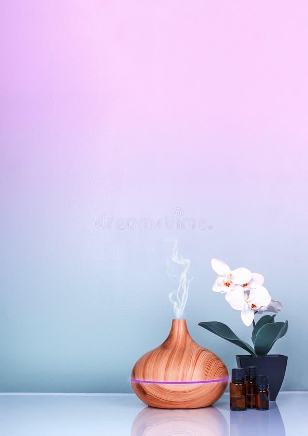 Elektrisk aromdiffusor för nödvändiga oljor, oljaflaskor och blommor på ljust - grön yttersida med reflexion arkivbild