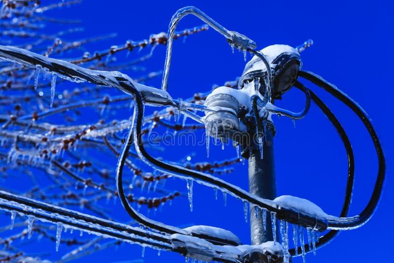 Elektrisk askinstallation med kristallistappar som hänger från trådarna Vädervinterkatastrof i Nordamerika Iskatastrof arkivfoton