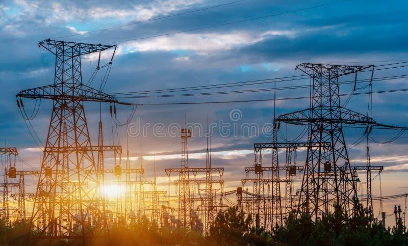 Elektrisk avdelningskontor för fördelning med kraftledningar och transformatorer, på solnedgången royaltyfri fotografi