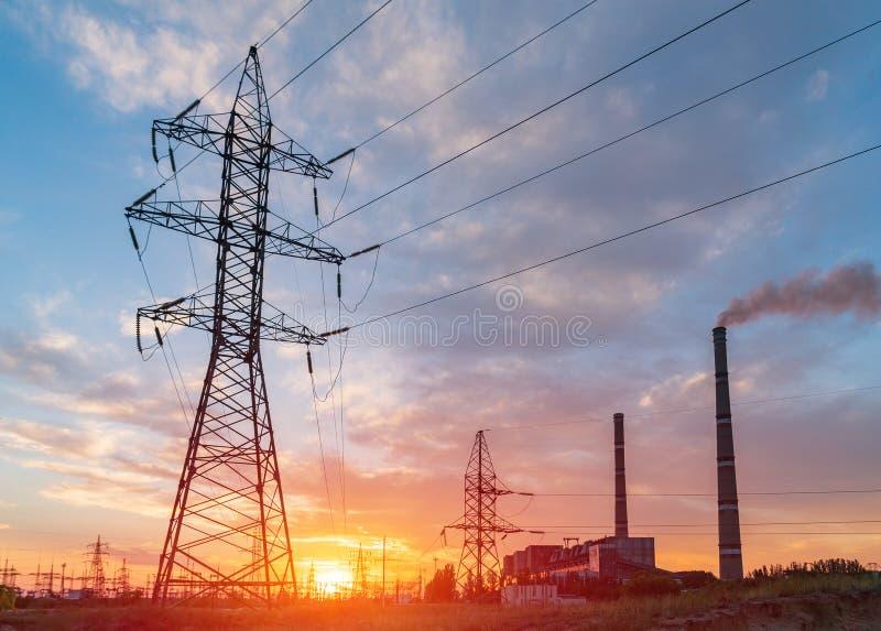 Elektrisk avdelningskontor för fördelning med kraftledningar och transformatorer, på solnedgången royaltyfria foton