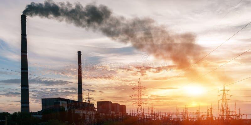 Elektrisk avdelningskontor för fördelning med kraftledningar och transformatorer, på solnedgången arkivbilder
