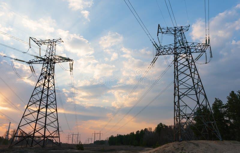 Elektrisk avdelningskontor f?r f?rdelning med kraftledningar och transformatorer, p? solnedg?ngen royaltyfri fotografi
