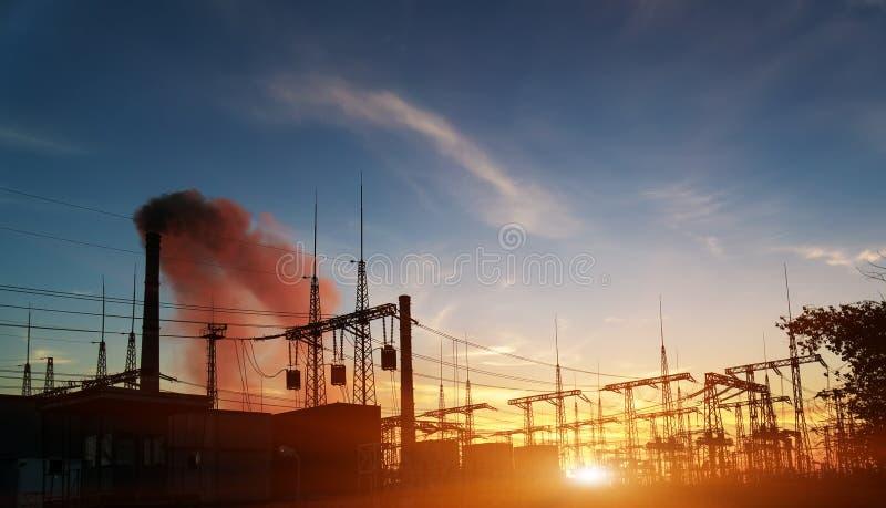Elektrisk avdelningskontor f?r f?rdelning med kraftledningar och transformatorer, p? solnedg?ngen royaltyfri bild