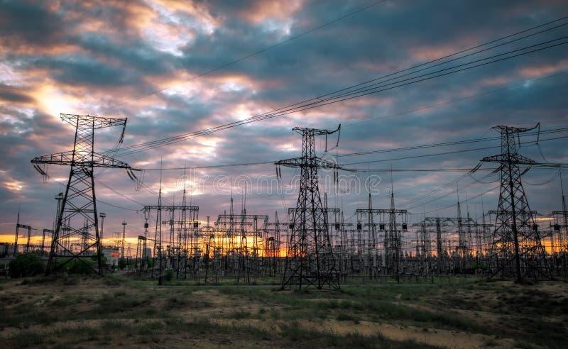 Elektrisk avdelningskontor med kraftledningar och transformatorer, på solnedgången royaltyfri foto
