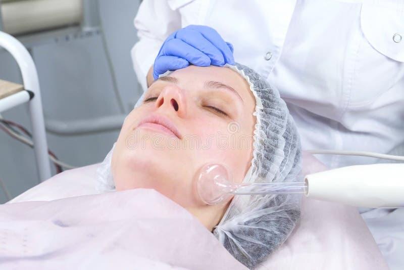 Elektrisk darsonval terapi för skönhetbehandlingansiktsbehandling på cosmetologykliniken arkivfoton