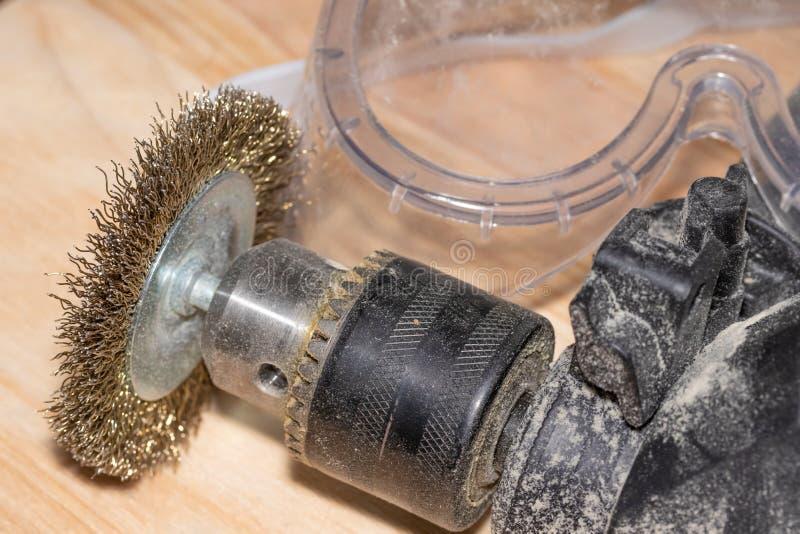 Elektrisk drillborr med disketten för att arbeta träyttersidor och skyddsglasögon på en träsnickeritabell royaltyfri bild