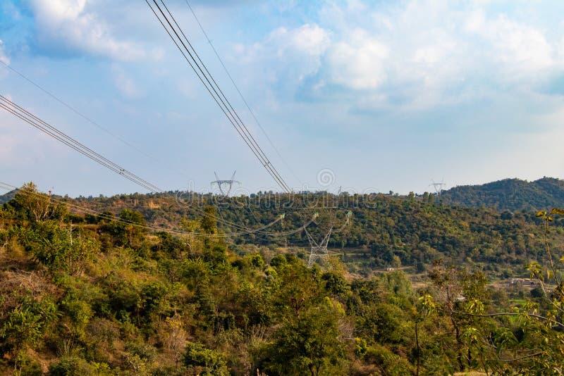Elektrisk hög pelare för volatgekraftledningtorn på ängkulleområde framme av blå himmel och moln royaltyfria foton