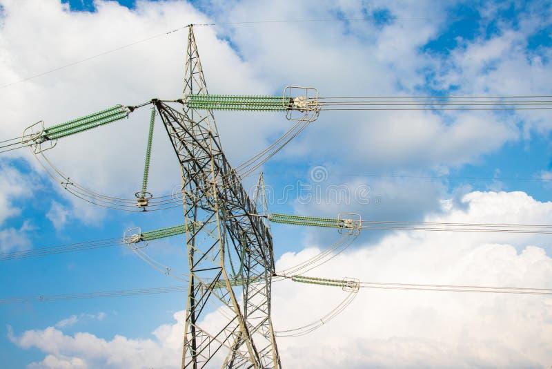 Elektrisk hög pelare för volatgekraftledningtorn på ängkulleområde framme av blå himmel och moln arkivbilder