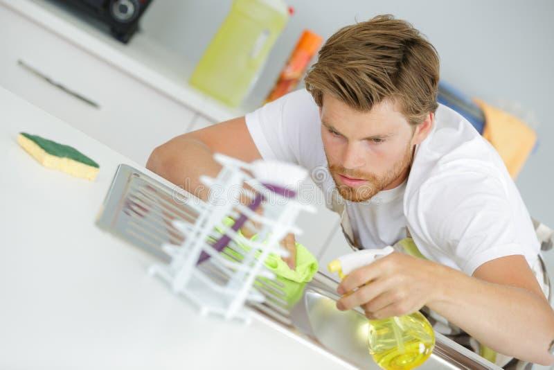 Elektrisk hob för manlig arbetarlokalvård på countertopen med torkduken royaltyfria foton