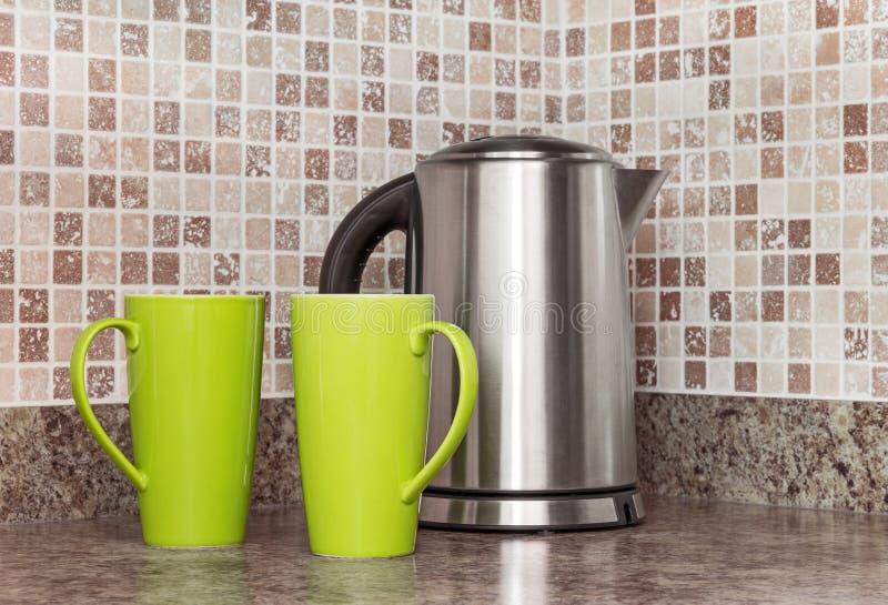Elektrisk kokkärl och koppar i köket arkivbilder