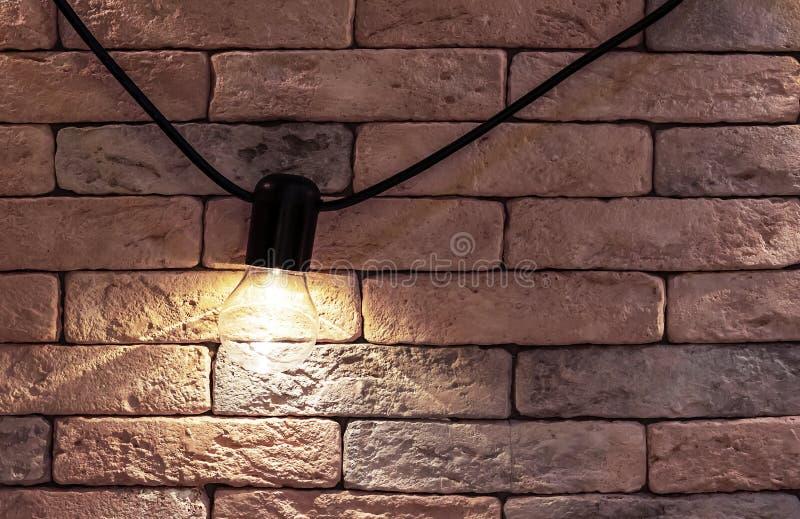 Elektrisk lampa på en bakgrund för tegelstenvägg Vindstilinre royaltyfri foto