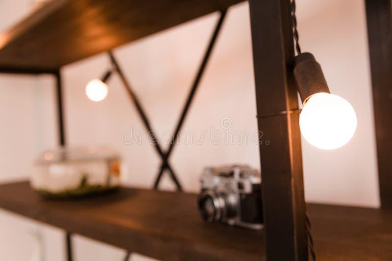 Elektrisk lampa som en dekor på en bokhylla royaltyfria bilder