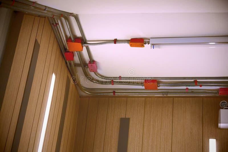 Elektrisk ledningsnät- och leda i röranslutning inom byggnaden arkivbild