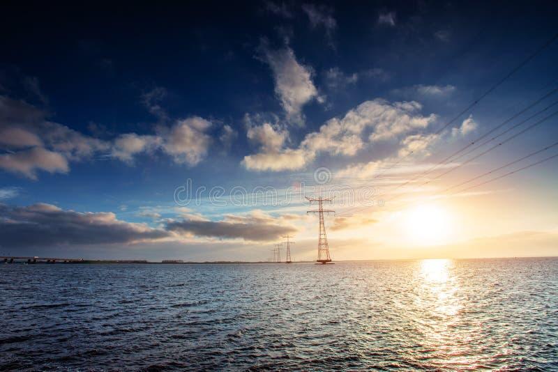 Elektrisk linje över - vatten under en fantastisk solnedgång fotografering för bildbyråer