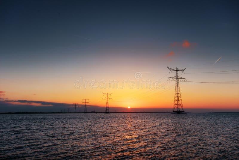 Elektrisk linje över - vatten under en fantastisk solnedgång arkivbilder